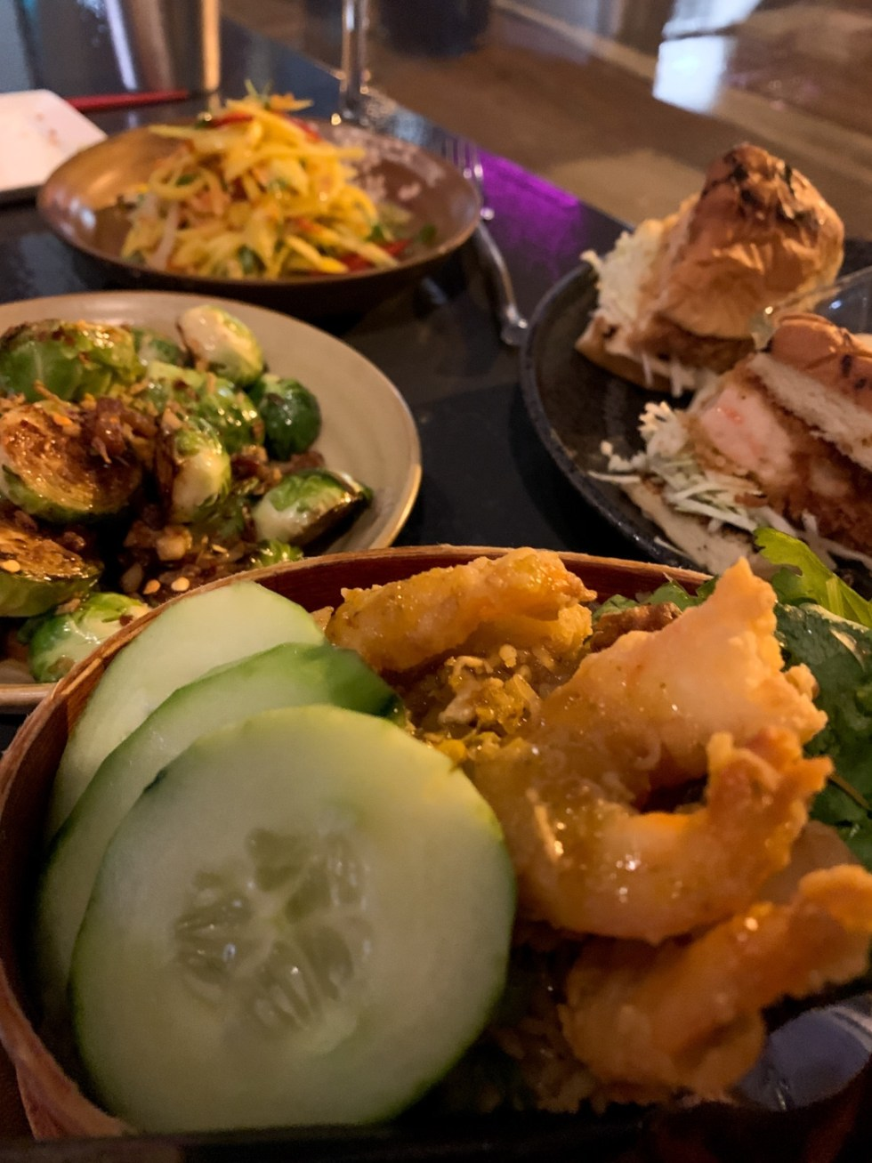23 Awesome Things To Do in Durham - I'm Fixin' To - @imfixintoblog | Things to do in Durham by popular NC travel blog, I'm Fixin' To: image of a fried shrimp and cucumber salad, glazed Brussel sprouts, and chicken sandwich.