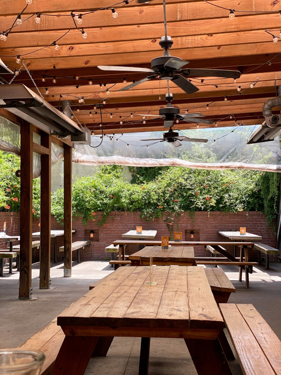 23 Awesome Things To Do in Durham - I'm Fixin' To - @imfixintoblog | Things to do in Durham by popular NC travel blog, I'm Fixin' To: image of a outdoor seating area with wooden picnic table, bistro lighting, and metal ceiling fans.