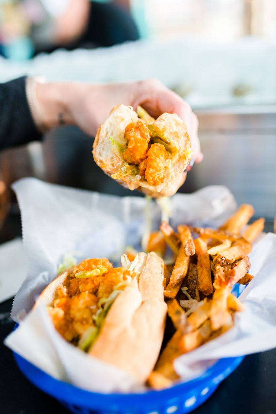 Raleigh Oyster Crawl - I'm Fixin' To - @mbg0112 | Raleigh Oyster Crawl by popular North Carolina blog, I'm Fixin' To: image of a woman holding a fried oyster sandwich over a blue plastic basket filled with fries.