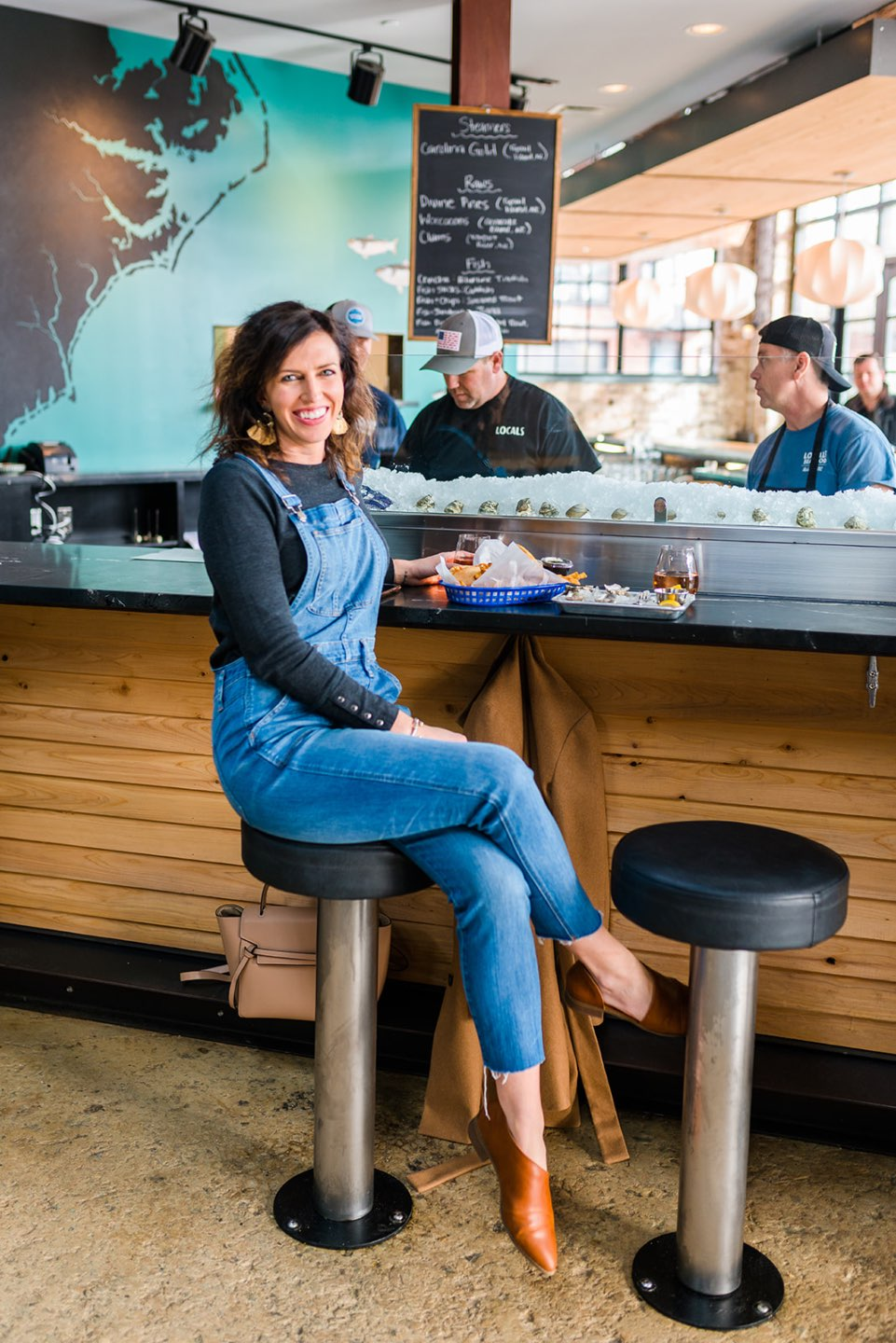Raleigh Oyster Crawl - I'm Fixin' To - @mbg0112 | Raleigh Oyster Crawl by popular North Carolina blog, I'm Fixin' To: image of a woman wearing overalls a long sleeve grey shirt and brown mules and sitting at a bar next to a tray of oysters.