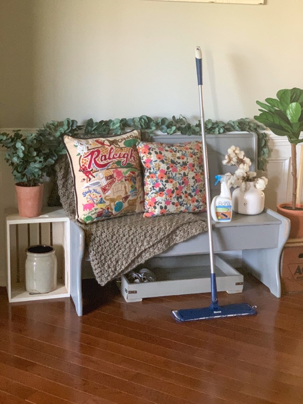 Keeping Our Floors Clean with Bona Essentials - I'm Fixin' To - @mbg0112 | Keeping Our Floors Clean with Bona Essentials by popular lifestyle blog, I'm Fixin' To: image of a bottle of Bona Essentials Hardwood Floor Deep Cleaner and a Bona Essentials Mop next to a grey wooden bench.