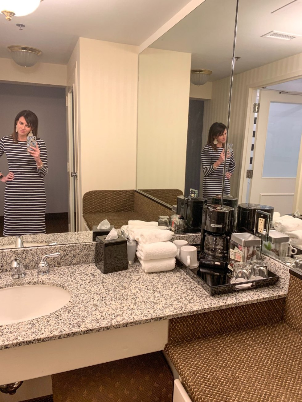 A Night at the O.Henry Hotel In Greensboro, NC - I'm Fixin' To - @mbg0112 | A Night at the O.Henry Hotel In Greensboro, NC by popular North Carolina blog, I'm fixin' To: image of a woman in a black and white stripe dress taking a picture in the mirror at the O. Henry Hotel.
