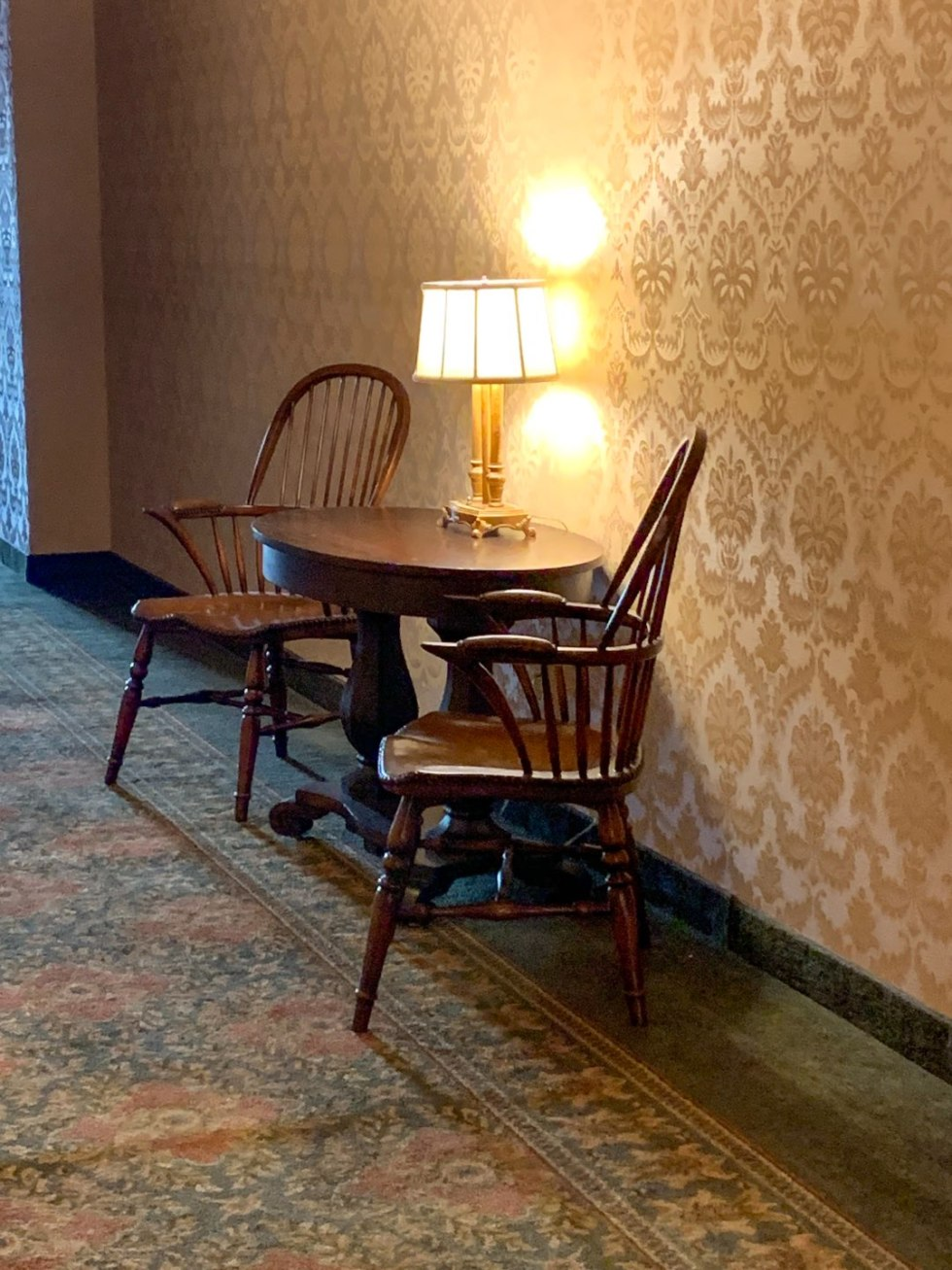 A Night at the O.Henry Hotel In Greensboro, NC - I'm Fixin' To - @mbg0112 | A Night at the O.Henry Hotel In Greensboro, NC by popular North Carolina blog, I'm fixin' To: image of a table with a lamp on it and two chairs in a hallway at the O. Henry Hotel.