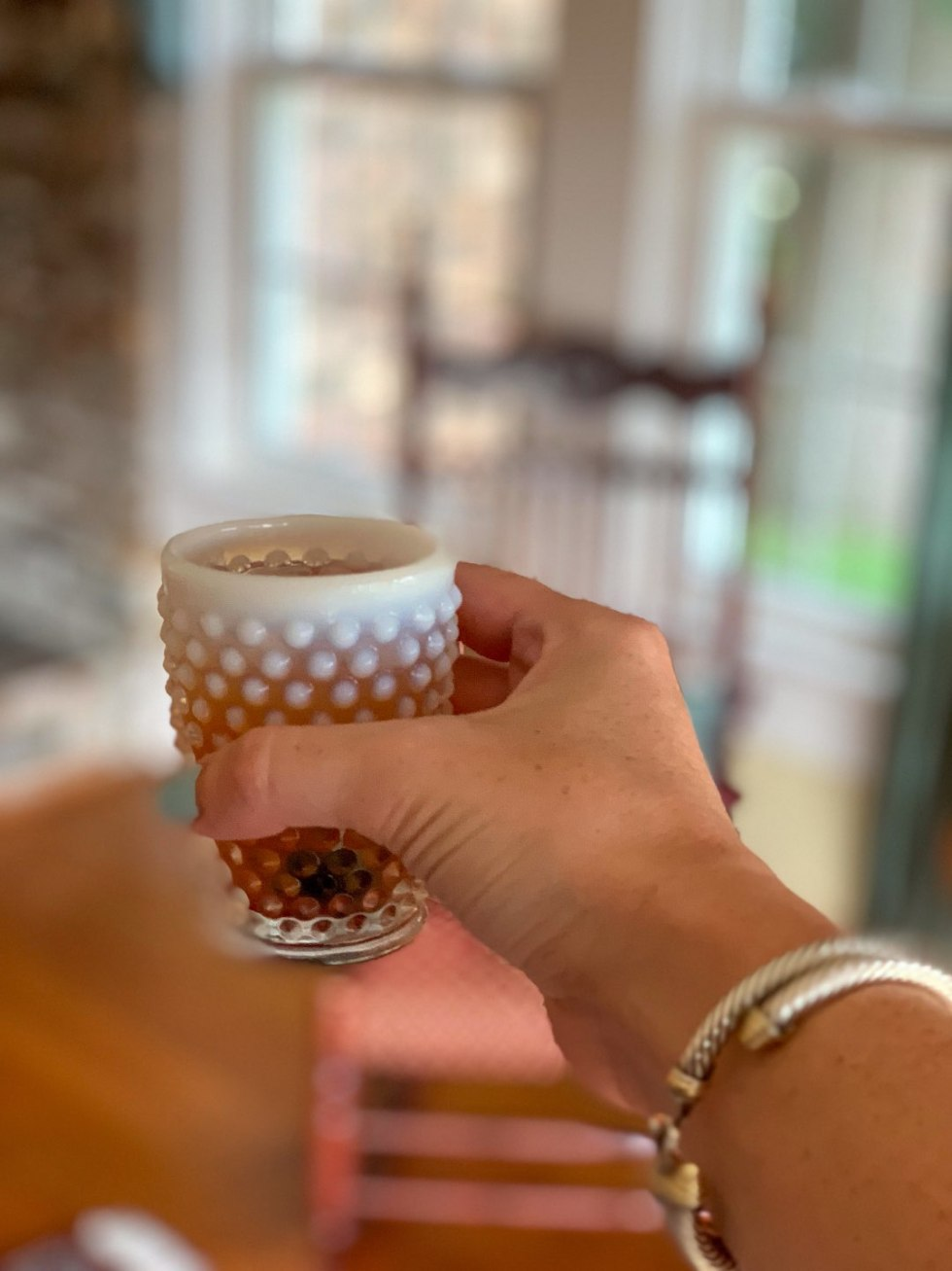 Welcome August + July 2019 Instagram Roundup - I'm Fixin' To - @mbg0112 | Welcome August + July 2019 Instagram Roundup by popular North Carolina life and style blog, I'm Fixin' To: image of woman holding a hobnail milk glass cup at Between Water and Main Bed and Breakfast.