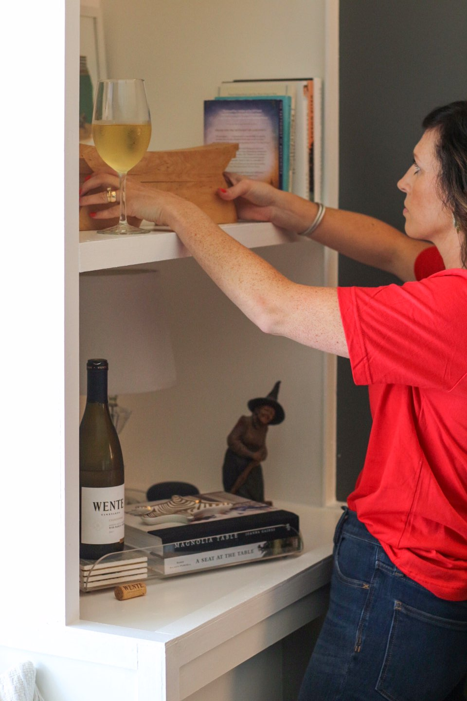 How I Make Time for Decorating with Wente Vineyards - I'm Fixin' To - @mbg0112 | How I Make Time for Decorating with Wente Vineyards by popular North Carolina lifestyle blog, I'm Fixin' To: image of a woman rearranging a book shelf in her home with a bottle and glass of Wente Vineyards wine close by