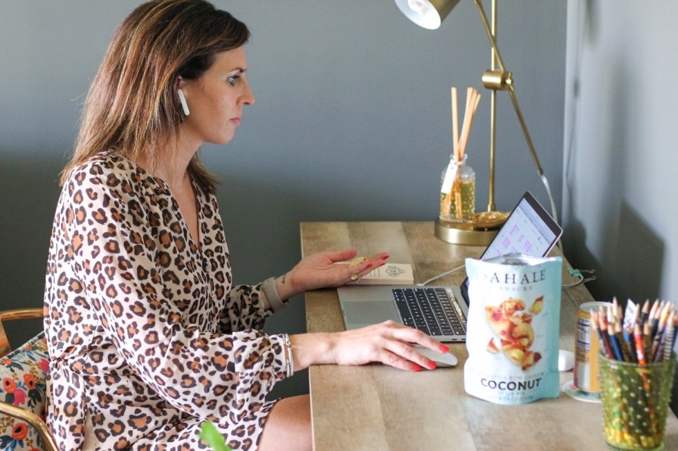 Quick Snack Ideas When You're On the Go by popular NC life and style blogger, I'm Fixin' To: image of a woman sitting at her computer desk and holding some Sahale Snacks coconut mix in her hands.