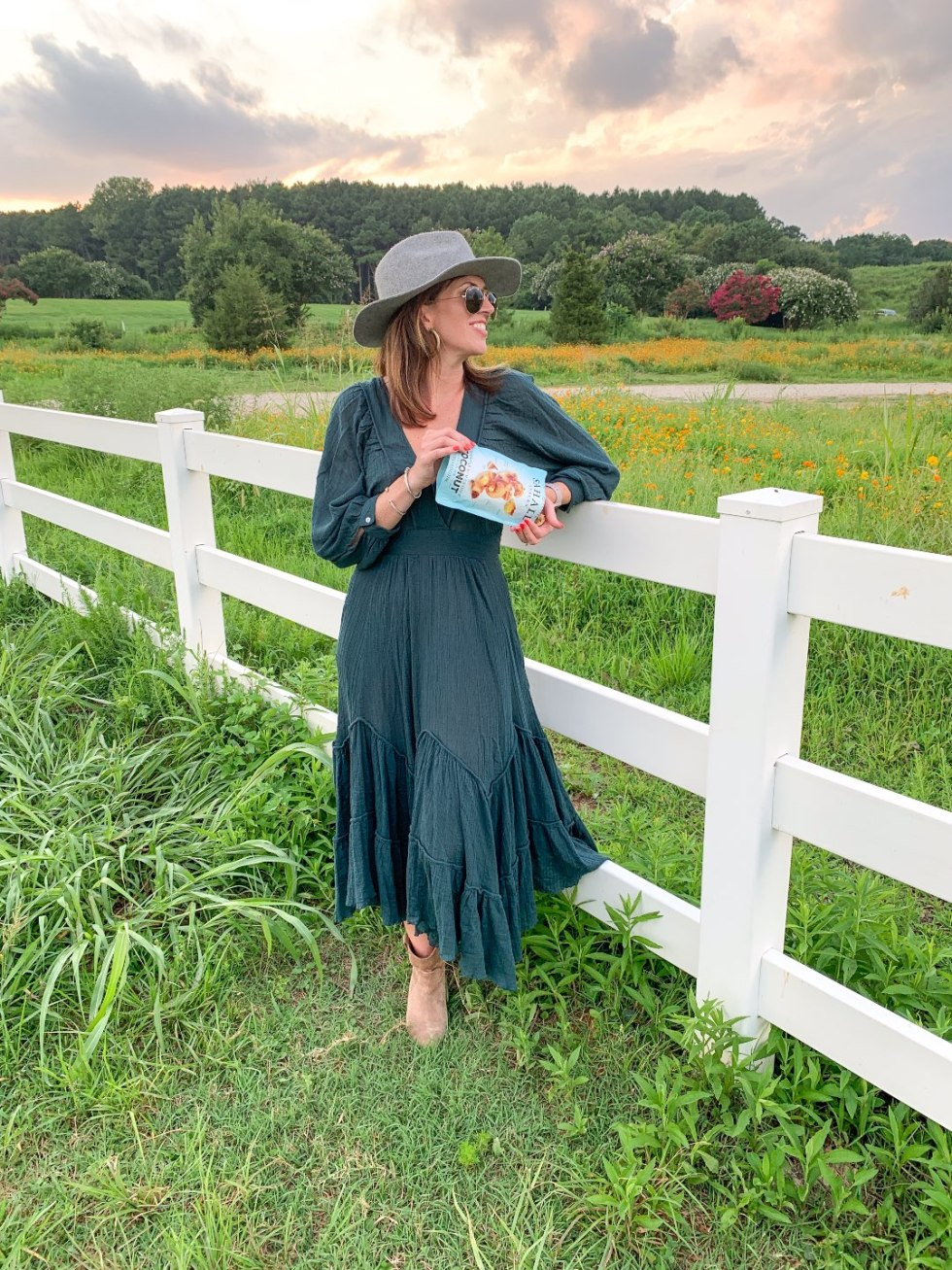 Quick Snack Ideas When You're On the Go by popular NC life and style blogger, I'm Fixin' To: image of a woman standing outside in a field and pouring a bag of Sahale Snacks coconut mix into her hands.