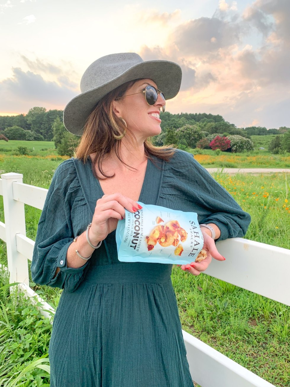 Quick Snack Ideas When You're On the Go - I'm Fixin' To - @mbg0112 | Quick Snack Ideas When You're On the Go by popular NC life and style blogger, I'm Fixin' To: image of a woman standing outside in a field and pouring a bag of Sahale Snacks coconut mix into her hands.