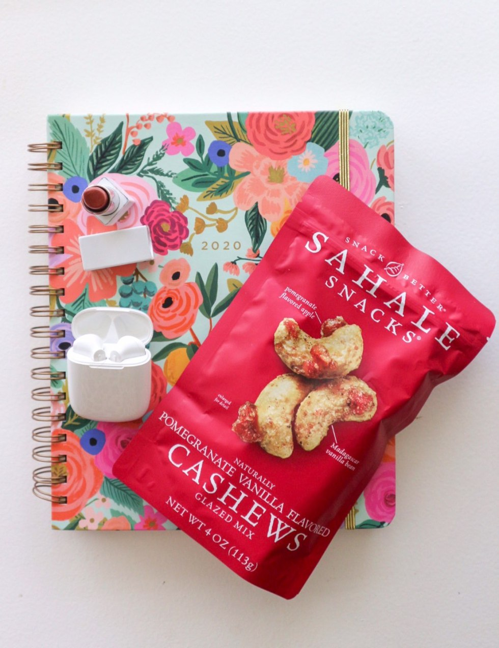 Quick Snack Ideas When You're On the Go by popular NC life and style blogger, I'm Fixin' To: image of a Rifle Paper Co. Planner, lipstick, airpods, and a bag of Sahale Snacks Pomegranate Vanilla Flavored Cashews.