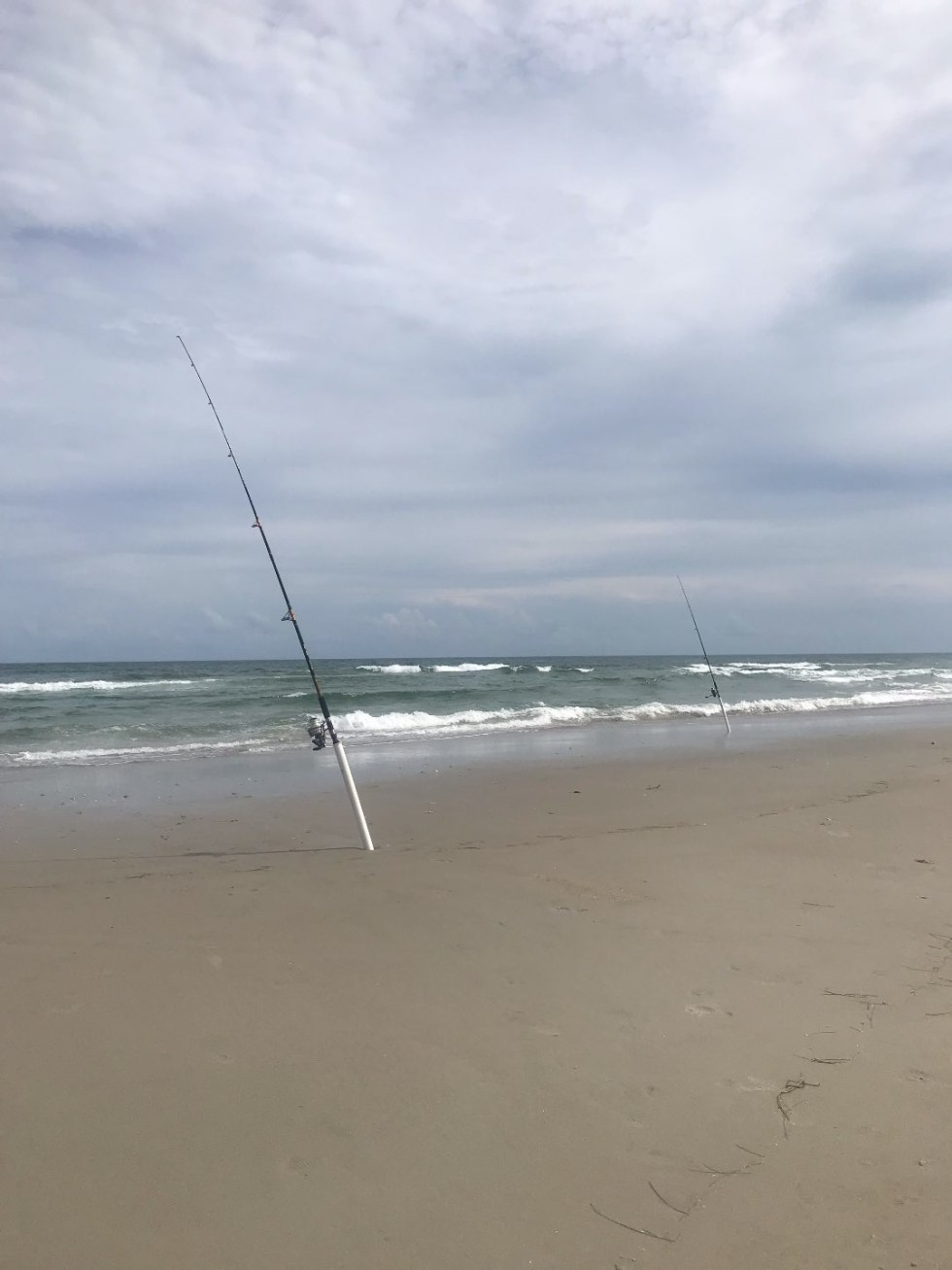 One Year Since  Hurricane Florence in North Carolina and How to Help Ocracoke by popular North Carolina blog, I'm Fixin' To: image of deep water fishing poles propped up in the sand at the beach.