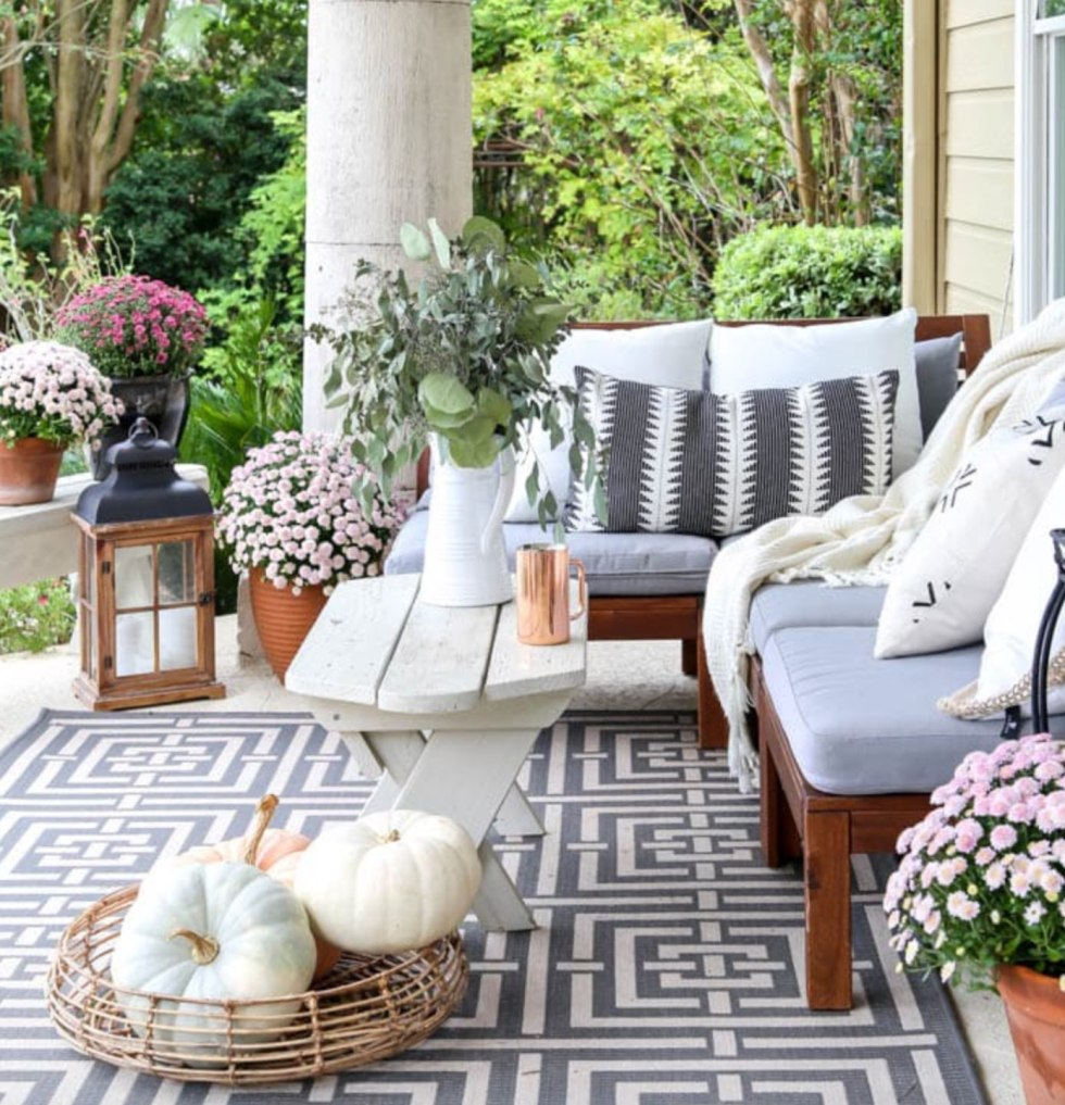 Inspiration Board: Fall Front Porch Ideas by popular North Carolina life and style blog, I'm Fixin' To: image of a front porch decorated with potted purple mums and pumpkins.