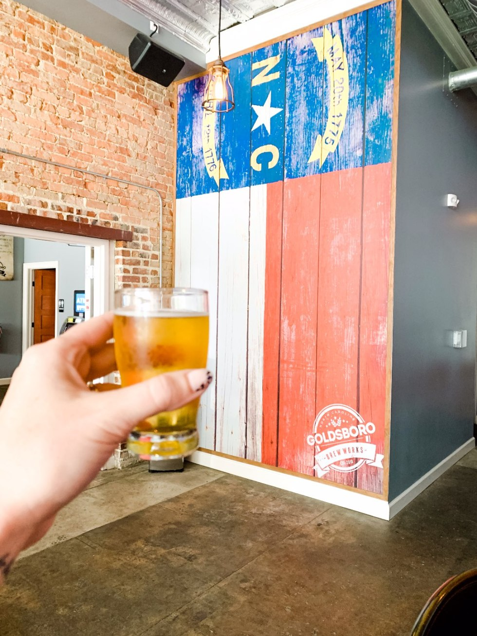 Eastern North Carolina Travel Guide: Top 10 Things to Do in Goldsboro NC by popular North Carolina blog, I'm Fixin' To: image of a woman holding up a glass of beer.