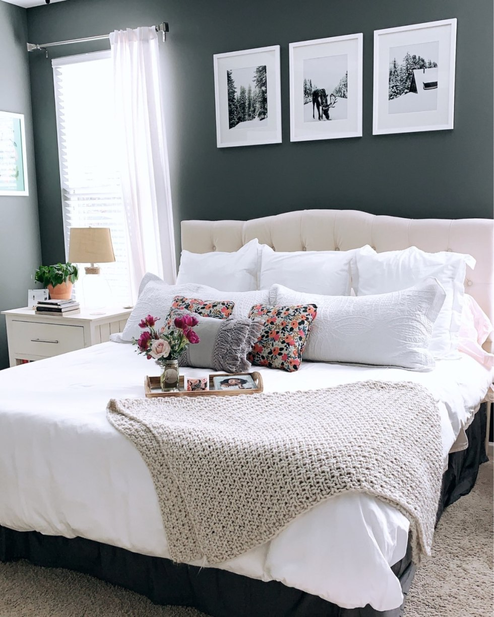 Second Year Updates to Our Ranch - I'm Fixin' To - @mbg0112 | Our Updated Ranch House by popular North Carolina life and style blog, I'm Fixin' To: image of a bedroom in an updated ranch house decorated with Headboard, Duvet, Prints,  Frames, Fringe Throw Pillow
