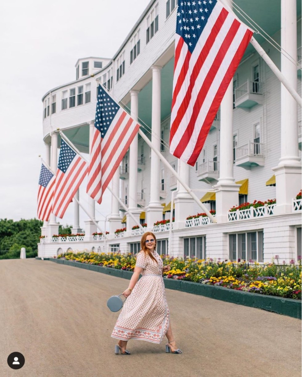 Top 12 Best Instagram Accounts to Follow - I'm Fixin' To - @mbg0112 | Top 12 Best Instagram Accounts to Follow by popular North Carolina lifestyle blog, I'm Fixin' To: image of a woman walking outside by a building displaying large American flags.