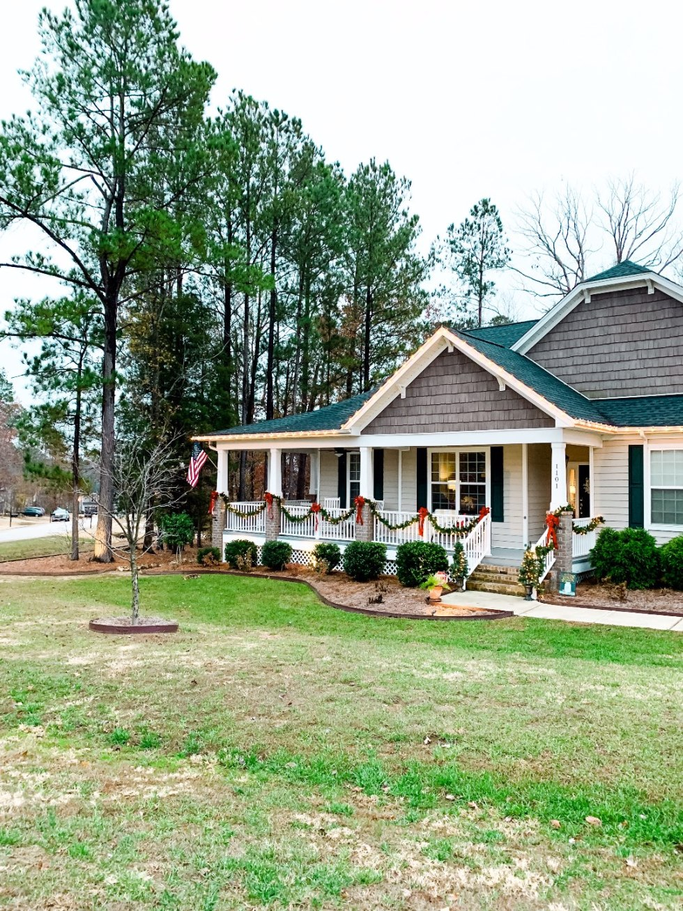 Holiday Home Decor Tour - I'm Fixin' To - @mbg0112 | Holiday Home Decor Tour by popular North Carolina life and style blog, I'm Fixin' To: image of a home exterior decorated with Pre-Lit Garland, Potted Pre-Lit Trees, Pottery Barn Door Mat (old, love this option), Plaid Mat, 3 Foot Pre-Lit Tree Buffalo Plaid Pillow Covers, and White Berry Wreath.
