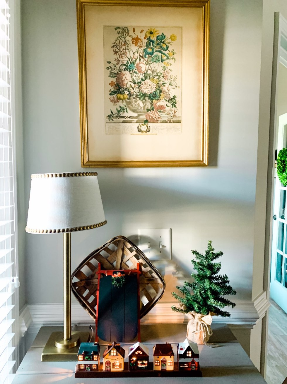 Holiday Home Decor Tour - I'm Fixin' To - @mbg0112 | Holiday Home Decor Tour by popular North Carolina life and style blog, I'm Fixin' To: image of a table with a Christmas village, mini pine tree, and decorative sled on it.