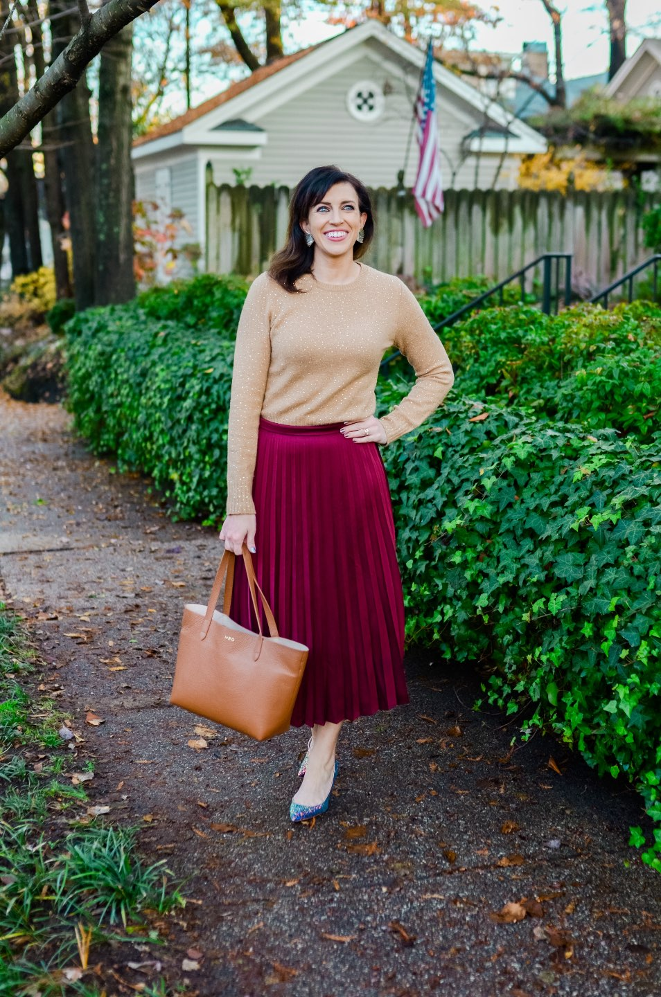 Holiday Style and Outfit Inspiration - I'm Fixin' To - @mbg0112 | Holiday Style and Outfit Inspiration by popular North Carolina fashion blog, I'm Fixin' To: image of a woman outside wearing a J. Crew Gemstone sweater in supersoft yarn, J. Crew Pleated midi skirt, J. Crew Colette d'Orsay pumps in holographic glitter, Cuyana Small Structured Leather Tote, Nordstrom David Yurman Cable Classic Buckle Bracelet with 18K Gold, Nordstrom David Yurman Cable Classics Bracelet with 14K Gold, Nordstrom Mignonne Gavigan Earrings, and Sephora Bite Beauty lipstick.