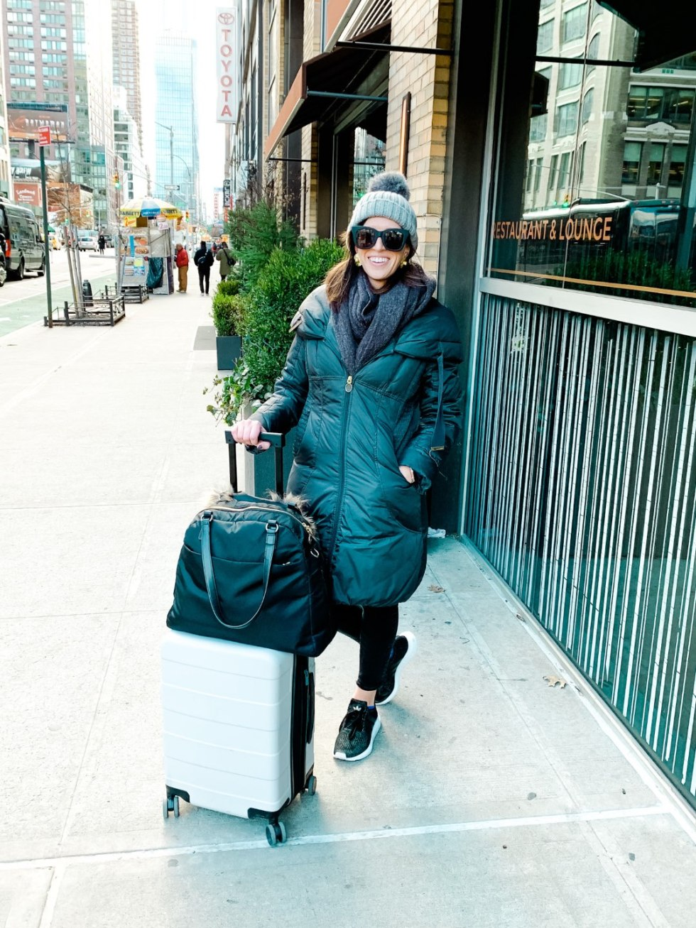 How to Pack a Carry-On - I'm Fixin To - @mbg0112 | How to Pack a Carry On for Flying by popular Raleigh travel blog, I'm Fixin' To: image of a woman standing outside with her carry on luggage.