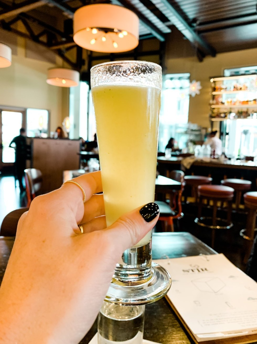 Where to Get Brunch in Raleigh: the 7 Best Spots - I'm Fixin' To - @mbg0112 | Brunch in Raleigh by popular Raleigh blog, I'm Fixin To: image of a woman holding an alcoholic beverage at Stir.