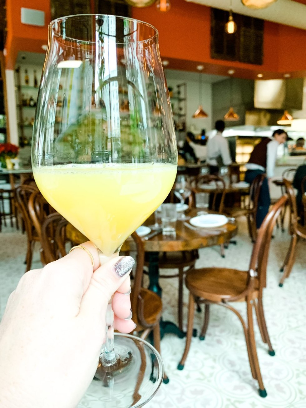 Brunch in Raleigh by popular Raleigh blog, I'm Fixin To: image of a woman holding a alcoholic beverage.