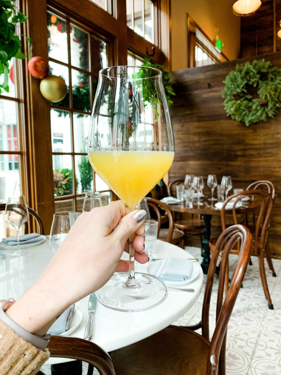 Brunch in Raleigh by popular Raleigh blog, I'm Fixin To: image of a woman holding a alcoholic drink at Rosewater Kitchen.