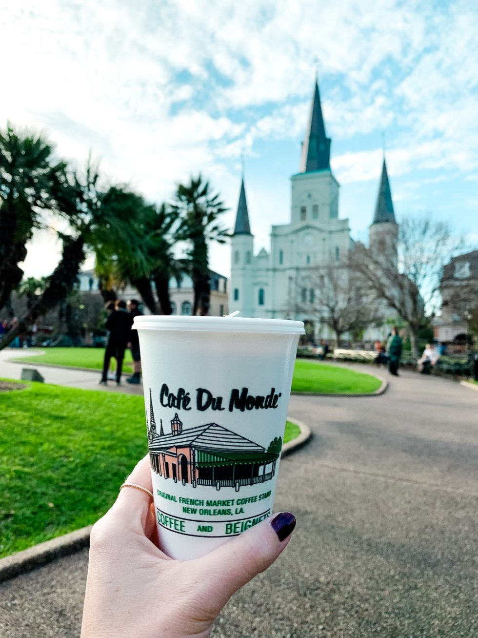 Girls Trip to New Orleans by popular US travel blog, I'm Fixin To: image of a woman holding a Cafe Du Monde coffee cup.