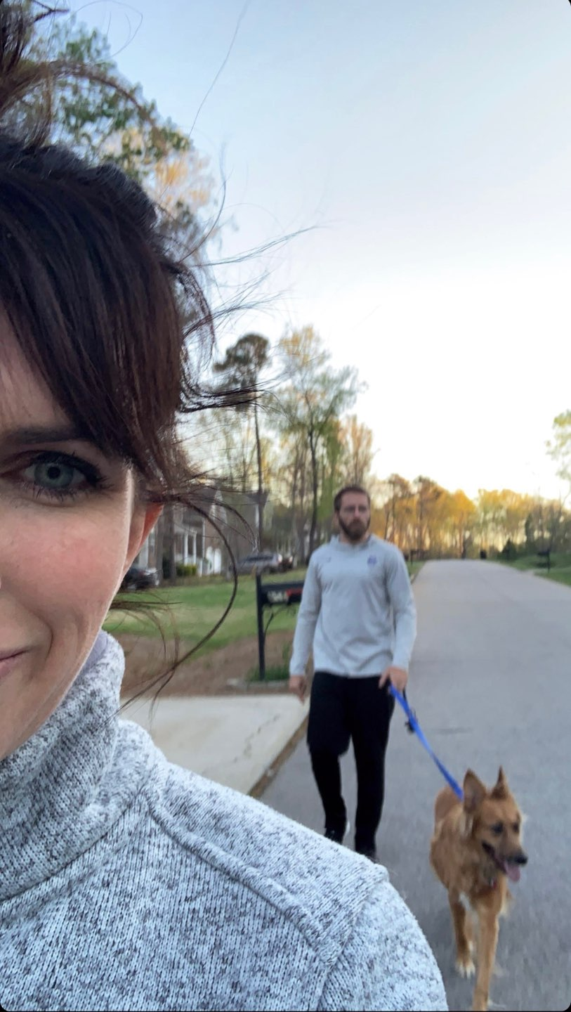 My Favorite Ways to Stay Active While Quarantined - I'm Fixin' To - @mbg0112 | How to Stay Active at Home by popular NC lifestyle blog, I'm Fixin' To: image of a woman and her husband walking their dog outside.
