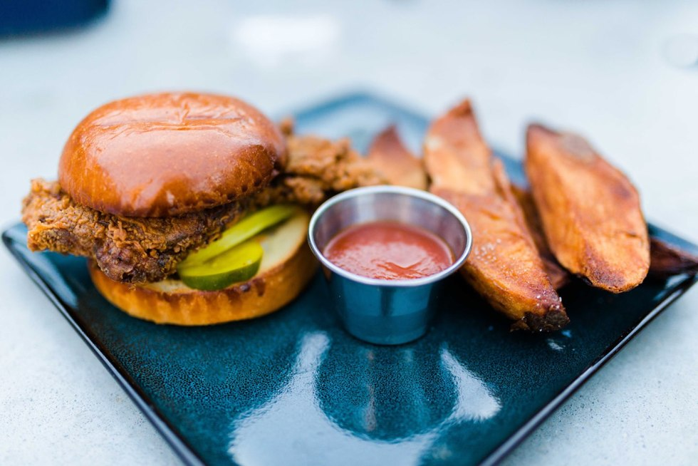 Top 5 Raleigh Restaurants with Curbside Delivery - I'm Fixin' To - @mbg0112 | Best Raleigh Restaurants by popular NC blog, I'm Fixin' To: image of Whiskey Kitchen fried chicken sandwich and potato wedges.