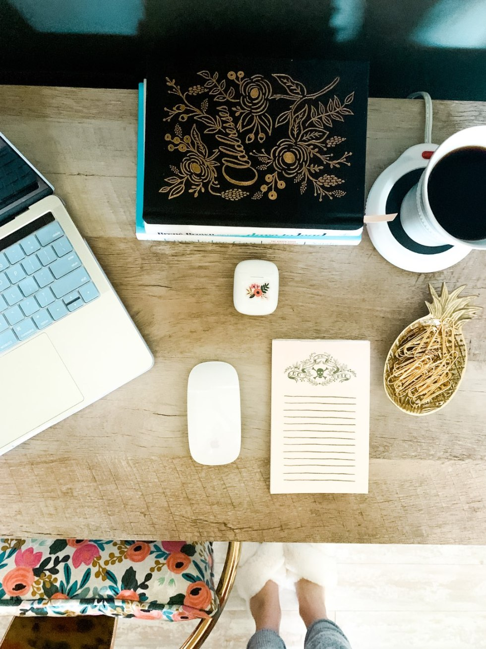 8 Items I am Loving for Working from Home - I'm Fixin' To - @mbg0112 | Work From Home Essentials by popular NC lifestyle blog, I'm Fixin To: image of a office desk with a laptop, candle warmer, pineapple trinket dish filled with gold paper clips, black address book, Rifle Paper Co. floral pillow, and floral note pad.