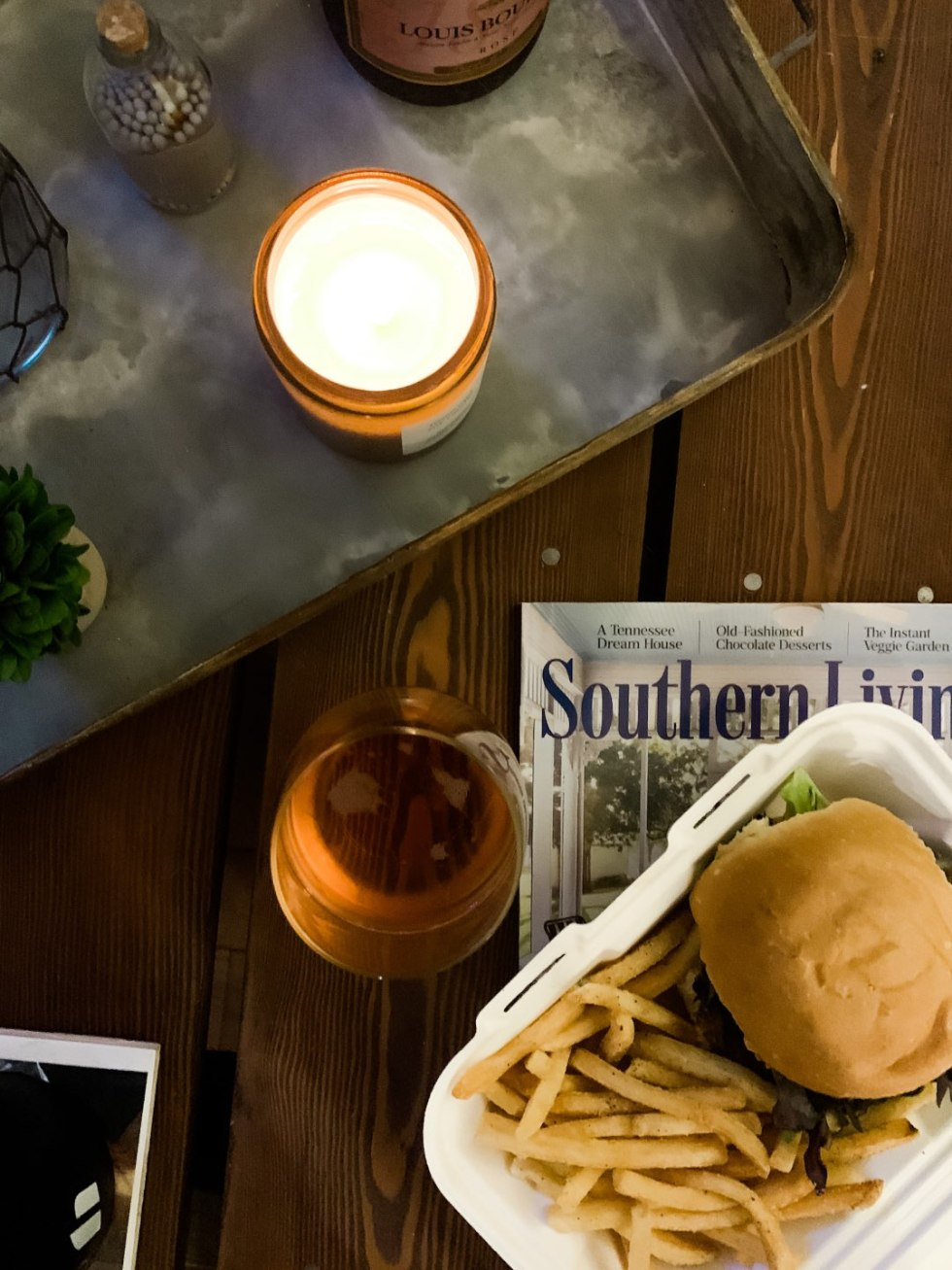 Top 10 Best Wines by popular N.C. lifestyle blog, I'm Fixin' To: image of a bottle of Louis Bouillot Perle d'Aurore Brut Rosé on a serving tray next to a takeout box containing a burger and fries.