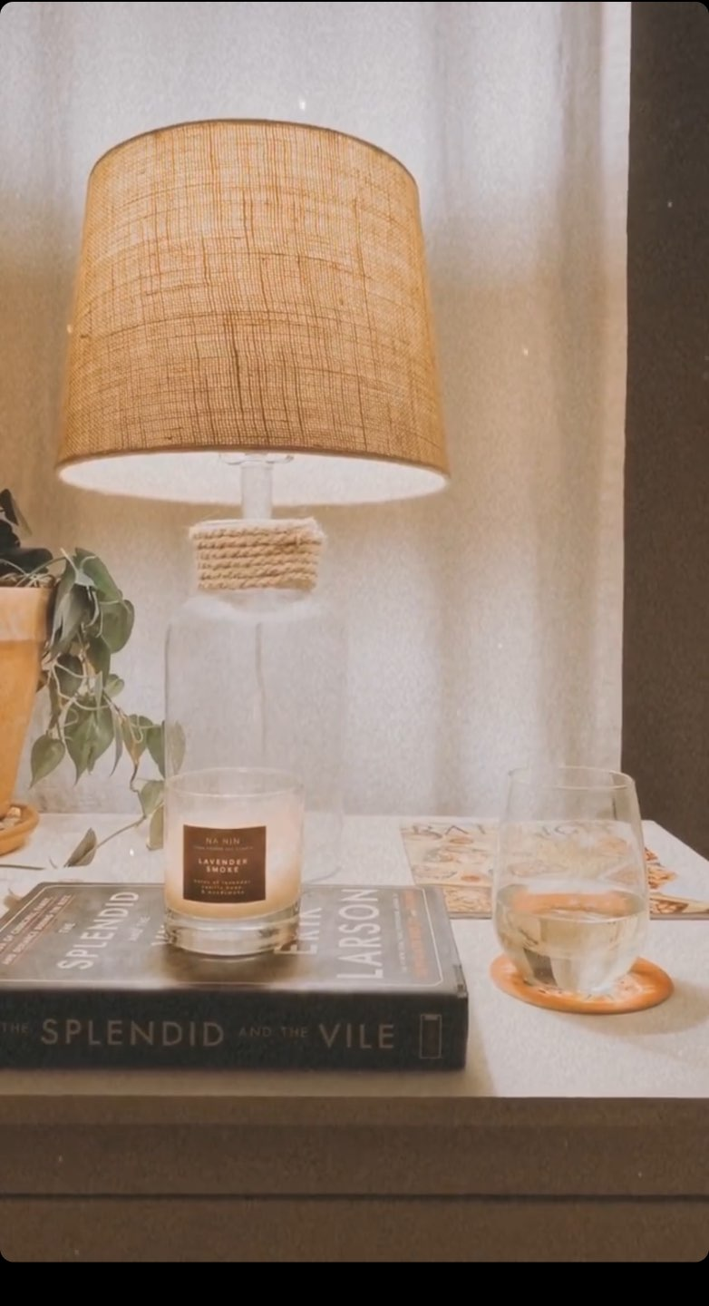 Home Fragrances for an Instant Pick-Me-Up during Quarantine (or Anytime!) - I'm Fixin' To - @mbg0112 | Home Fragrances by popular N.C. life and style blog, I'm Fixin' To: image of a night stand with a lamp, glass of water, The Splendid and the Vile book, and a Na Nin Lavender Smoke scented candle.