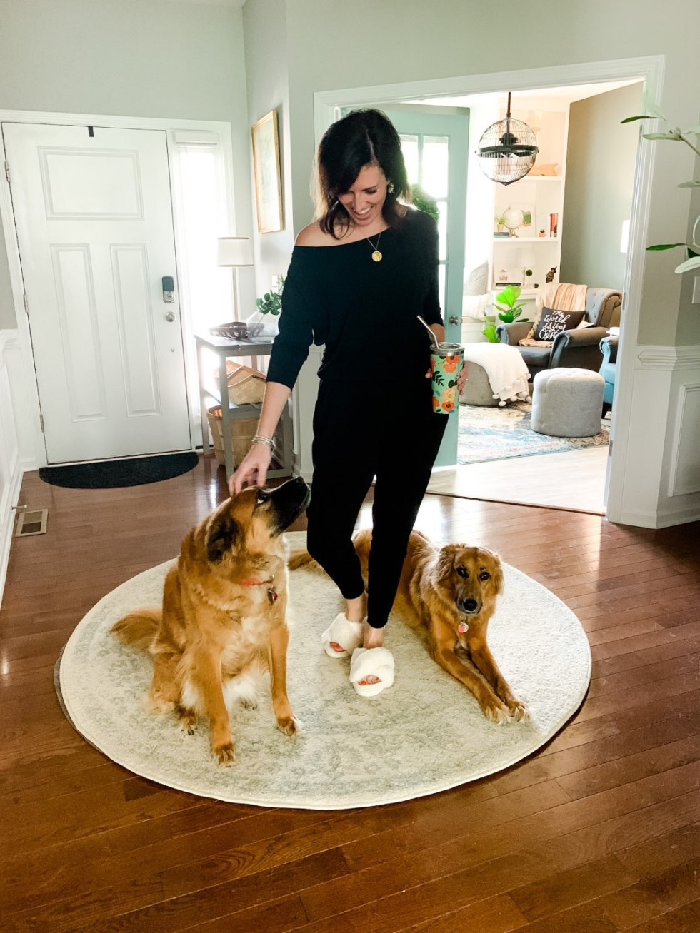 5 Stylish Teleworking Outfits for Women - I'm Fixin' To - @mbg0112 | Teleworking Outfits for Women by popular North Carolina fashion blog, I'm Fixin' To: image of a woman standing next to her dogs and wearing a black Michael Stars jumpsuit.