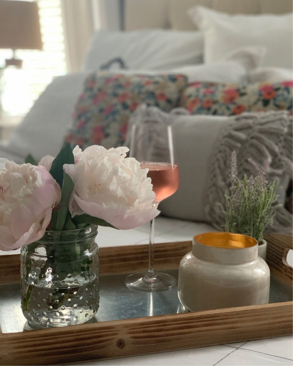 Summer Home Decor by popular North Carolina life and style blog, I'm Fixin' To: image of a a metal and wood tray containing a hobnail glass jar with peonies, a candle, a glass of wine, and a lavender plant.