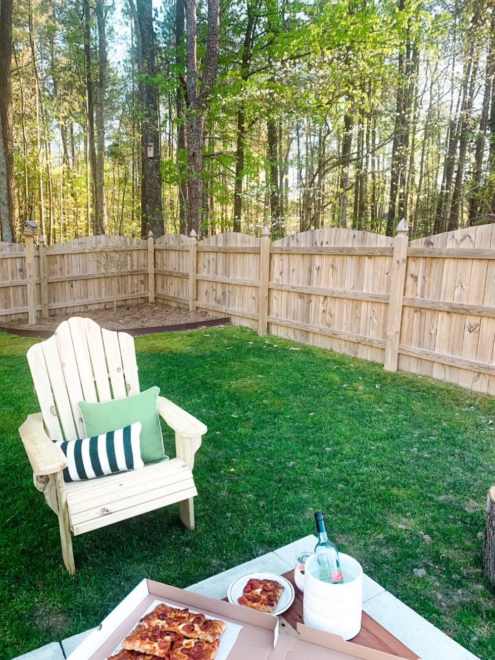 10 Backyard Picnic Essentials - I'm Fixin' To - @mbg0112 | Backyard Picnic by popular North Carolina lifestyle blog, I'm Fixin' To: image of a wooden adirondack chair with a black and white stripe pillow and a green pillow, box of pizza and a wine cooler with a bottle white wine in it.