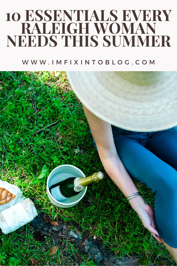10 Essentials Every Raleigh Woman Needs this Summer - I'm Fixin' To - @mbg0112 | What to Wear in Raleigh by popular North Carolina life and style blog, I'm Fixin' To: image of a woman wearing a straw sunhat and leggings while sitting on the grass next to a bottle of wine and a croissant sandwich.