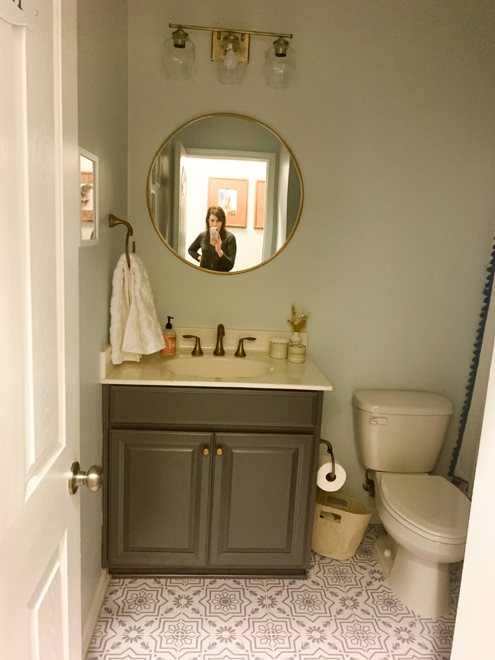 "How to Renovate a Guest Bathroom on a Budget: 5 Practical Tips - I'm Fixin' To - @mbg0112 | How to Update a Guest Bathroom on a Budget by popular North Carolina life and style blog: image of a guest bathroom decorated with Serena & Lily Hand Towels, Target 28"" Round Decorative Wall Mirror, Target 13"" Decorative Coiled Rope Square Base Tapered Basket, Etsy Snazzy Decal tile sticker, Serena and Lily shower curtain, a white bath mat Wayfair Nunes 3-Light Dimmable Antique Brass Vanity Light."