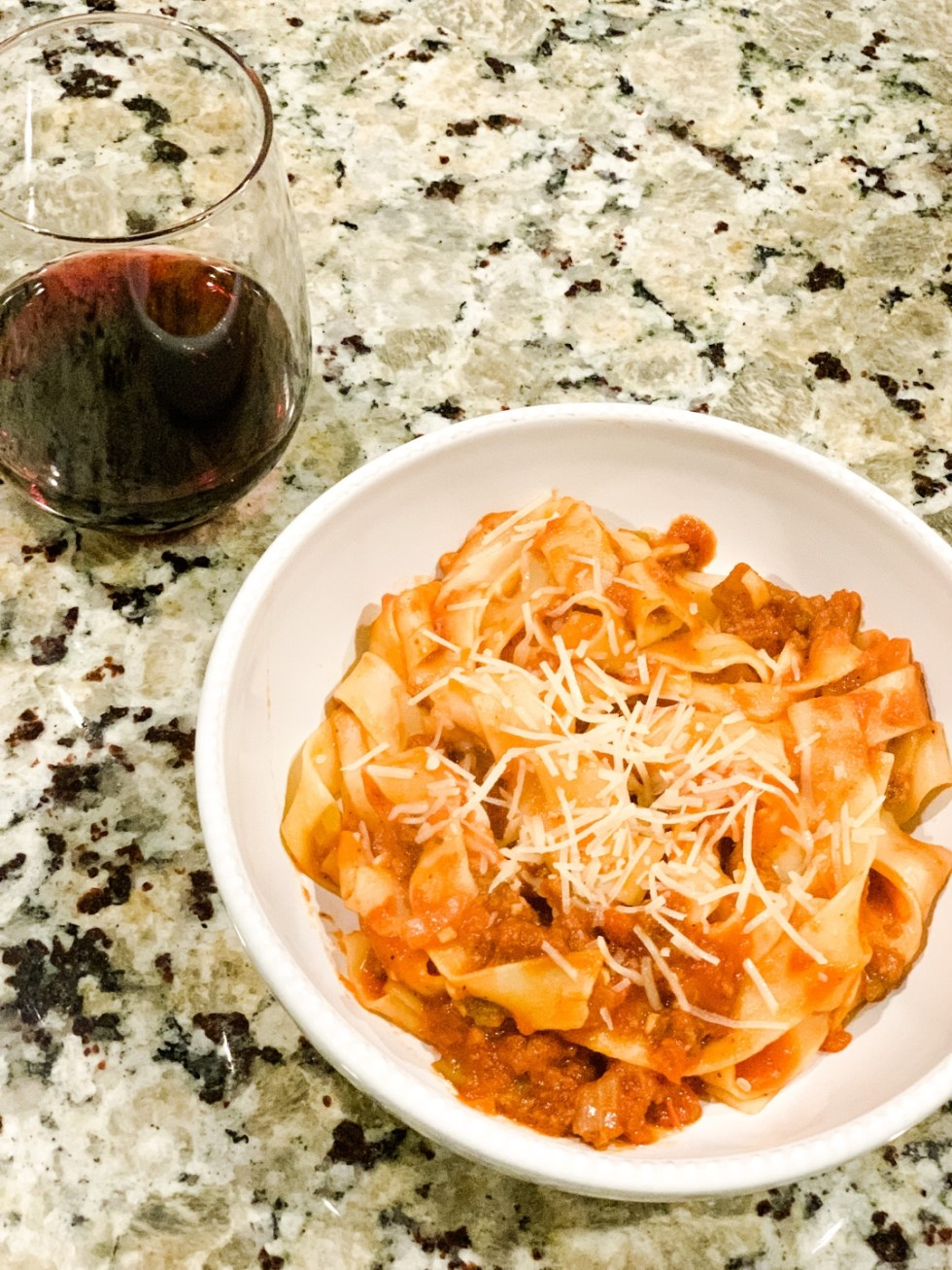 7 Recipes I Have Tried During Quarantine - I'm Fixin' To - @mbg0112 | Easy Recipes for Two by popular North Carolina lifestyle blog, I'm Fixin' To: image of a glass of red wine and some pasta in a white ceramic bowl.