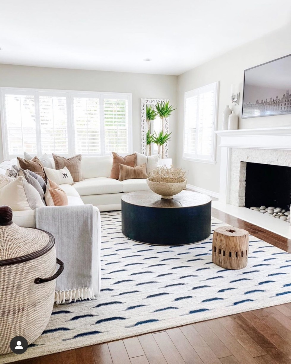 Living Room Inspiration by popular N.C. life and style blog, I'm Fixin' To: image of a Heart and Haven living room with a white sectional couch, round coffee table, and white and blue area rug.