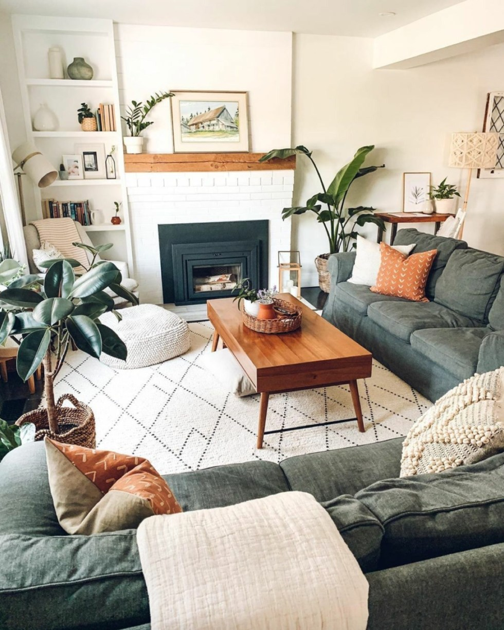 Inspiration Board: Living Room - I'm Fixin' To - @mbg0112 | Living Room Inspiration by popular N.C. life and style blog, I'm Fixin' To: image of a living room with a grey sectional couch, white fire place, black and white area rug, indoor plants, and a brown coffee table.
