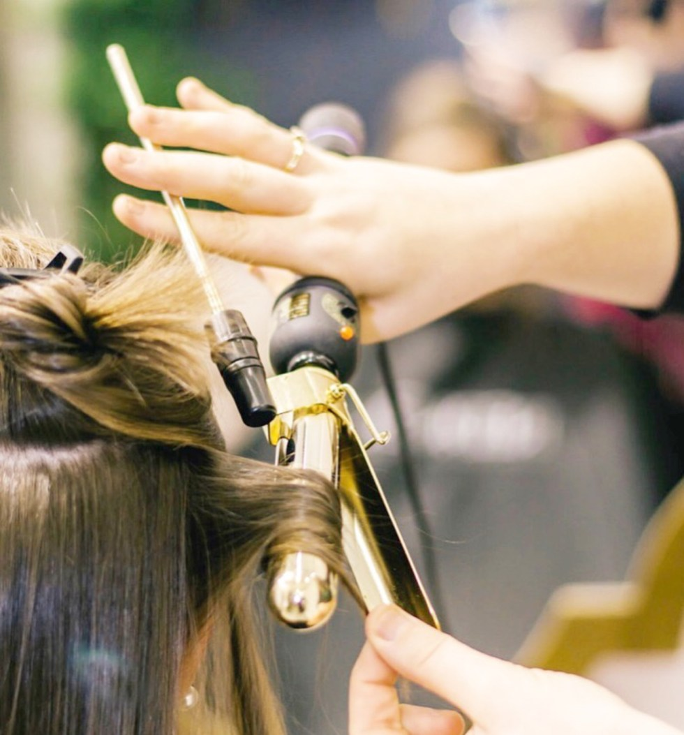 Salon Lofts Falls of Neuse Olive Park by popular N.C. lifestyle blog, I'm Fixin' To: image of a woman curling another woman's hair with a gold curling iron.