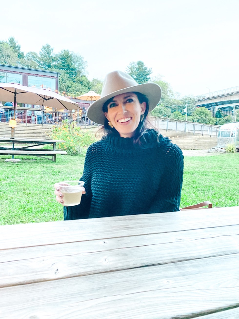 A Casual Weekend in Asheville: the Best Things to Do with your Dogs - I'm Fixin' To - @mbg0112   Weekend In Asheville by popular NC travel blog, I'm Fixin' To: image of a woman sitting outside at the Smokey Mountain Supper Club.