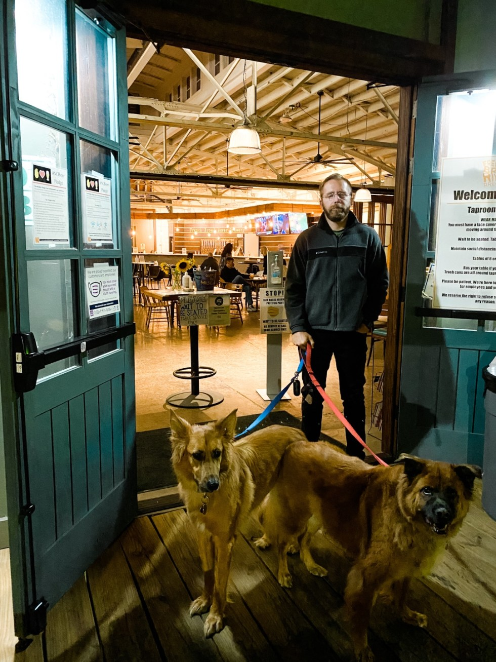 A Casual Weekend in Asheville: the Best Things to Do with your Dogs - I'm Fixin' To - @mbg0112   Weekend In Asheville by popular NC travel blog, I'm Fixin' To: image of a man and his two dogs standing outside the French Broad River Brewery.
