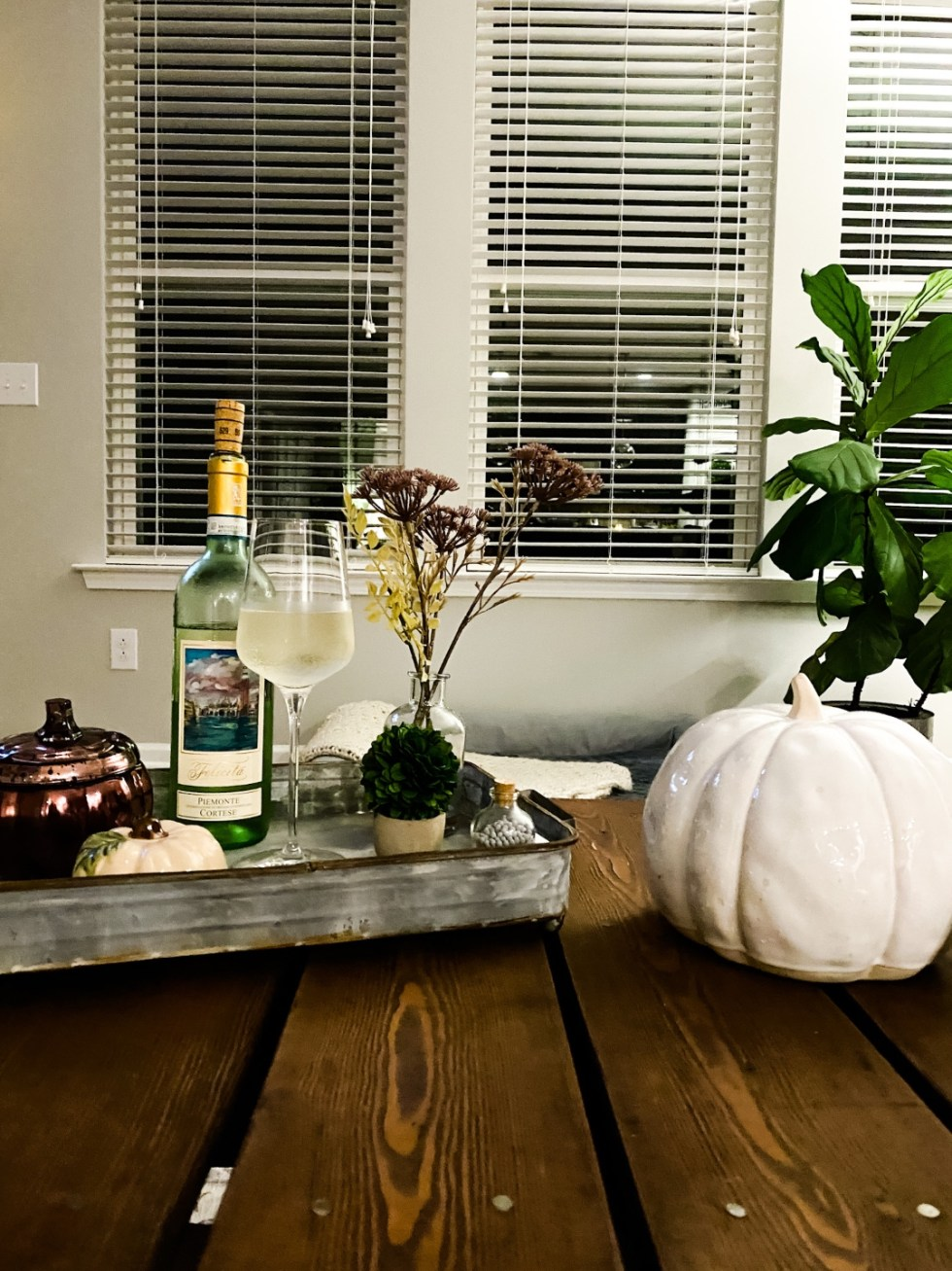 Target Fall Home Decor by popular N.C. life and style blog, I'm Fixin' To: image of a table set with a white ceramic pumpkin, metal serving tray, bottle of white wine, wine glass filled with white wine, and some ceramic pumpkins.