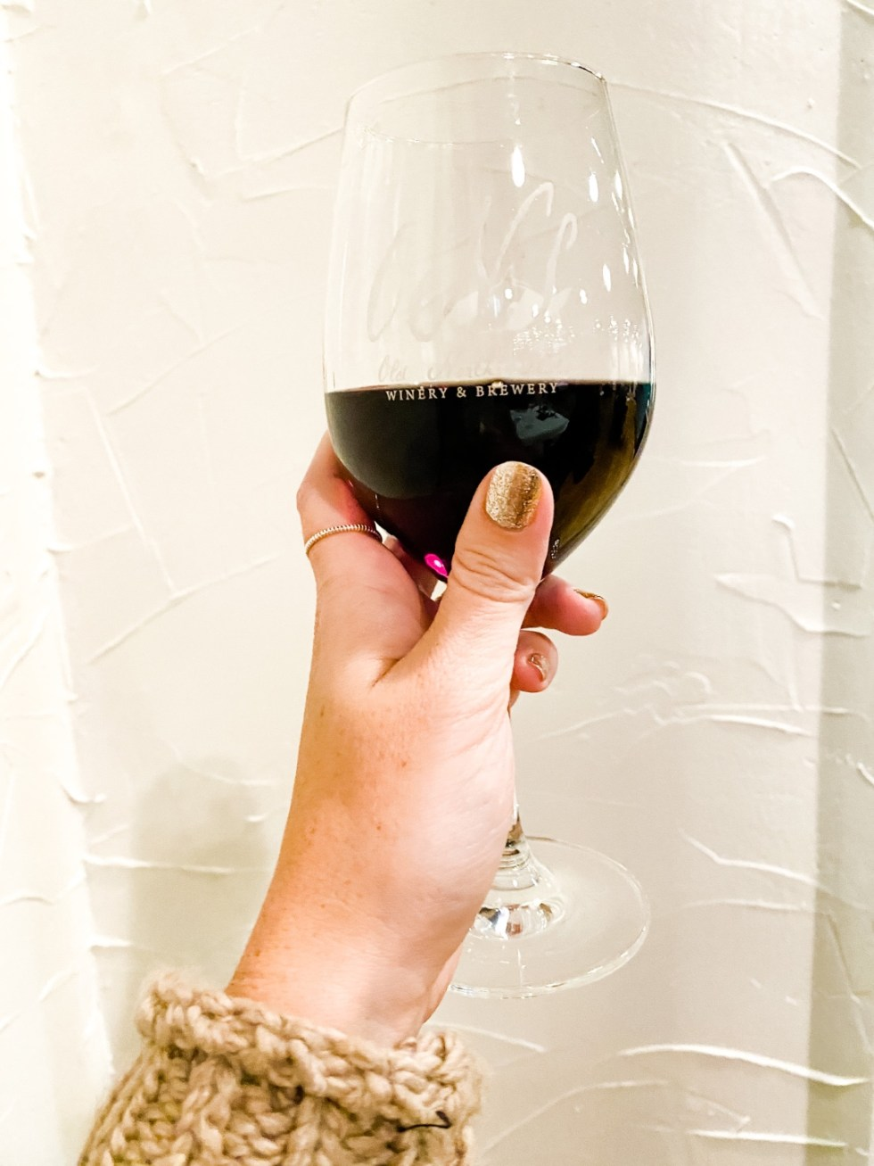 Western NC Wineries: 6 Wineries to Visit During your Next Girls' Weekend - I'm Fixin' To - @mbg0112 |Western NC Wineries by popular NC blog, I'm Fixin' To: image of a woman holding a glass of red wine at Old North State Winery.