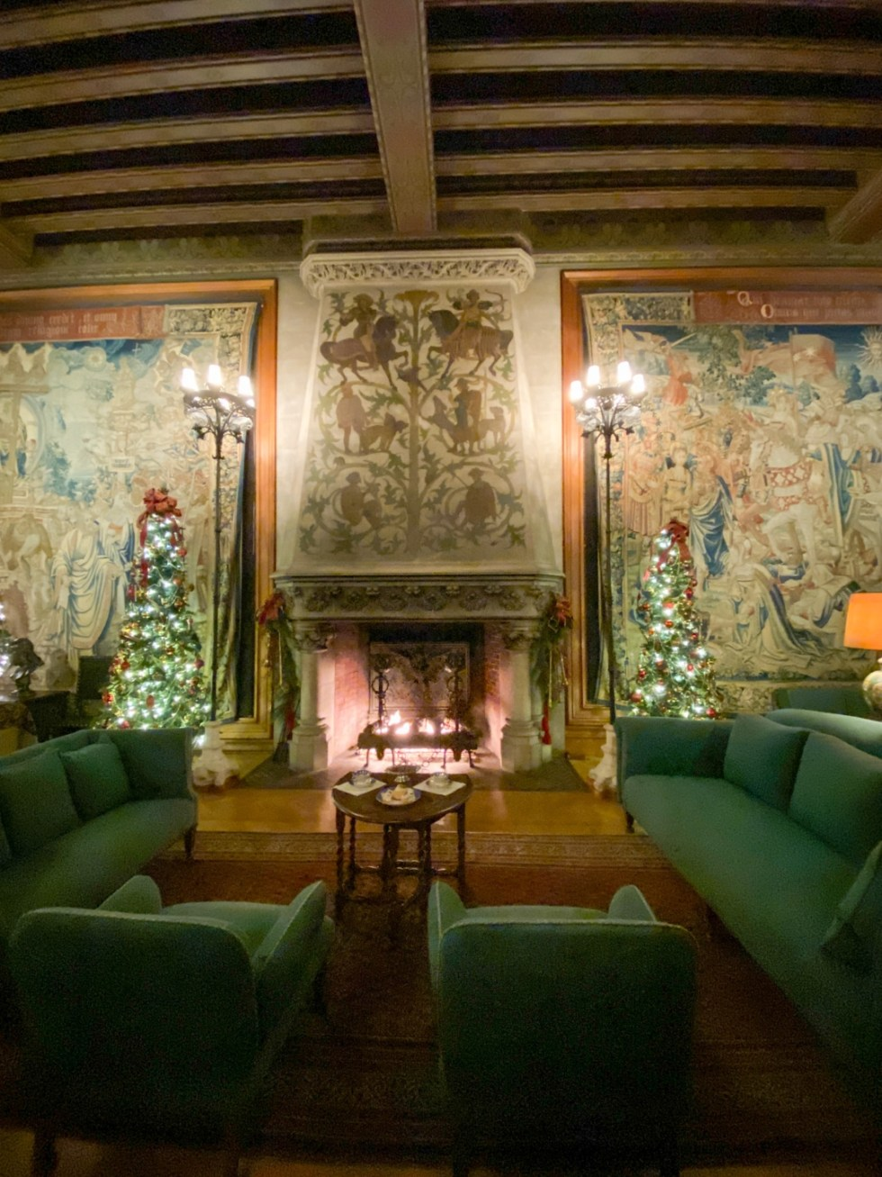 Christmas in Asheville: a Weekend Getaway During the Holidays - I'm Fixin' To - @imfixintoblog |Christmas in Asheville NC by popular NC lifestyle blog, I'm Fixin' To: image of green couches and chairs in front of a ornate fireplace at the Biltmore House.