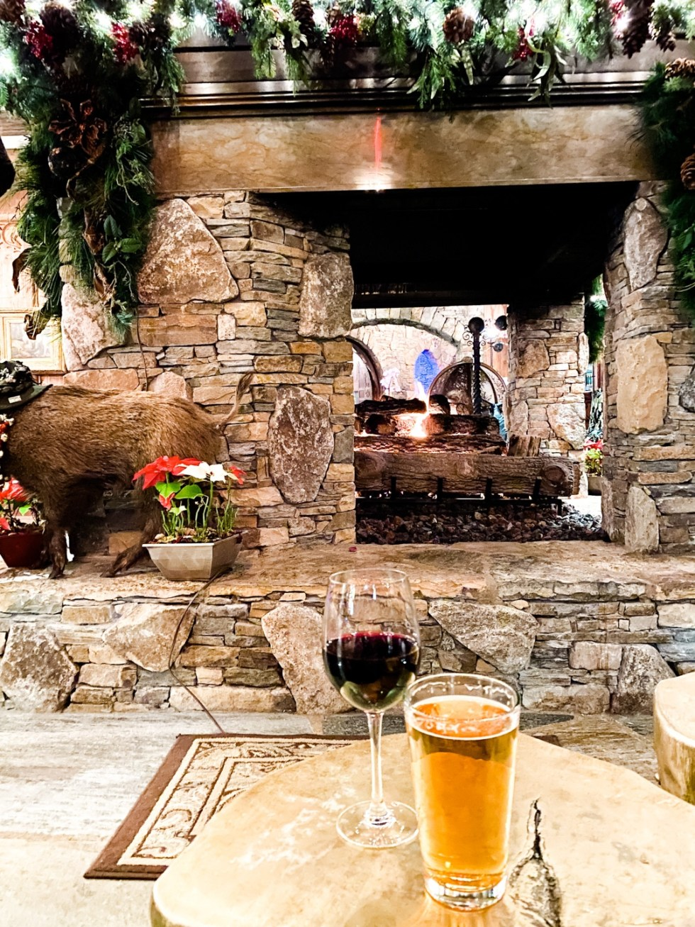 Christmas in Asheville: a Weekend Getaway During the Holidays - I'm Fixin' To - @imfixintoblog |Christmas in Asheville NC by popular NC lifestyle blog, I'm Fixin' To: image of a glass of beer and a glass of red wine on a table next to a fireplace at the red stag grill.