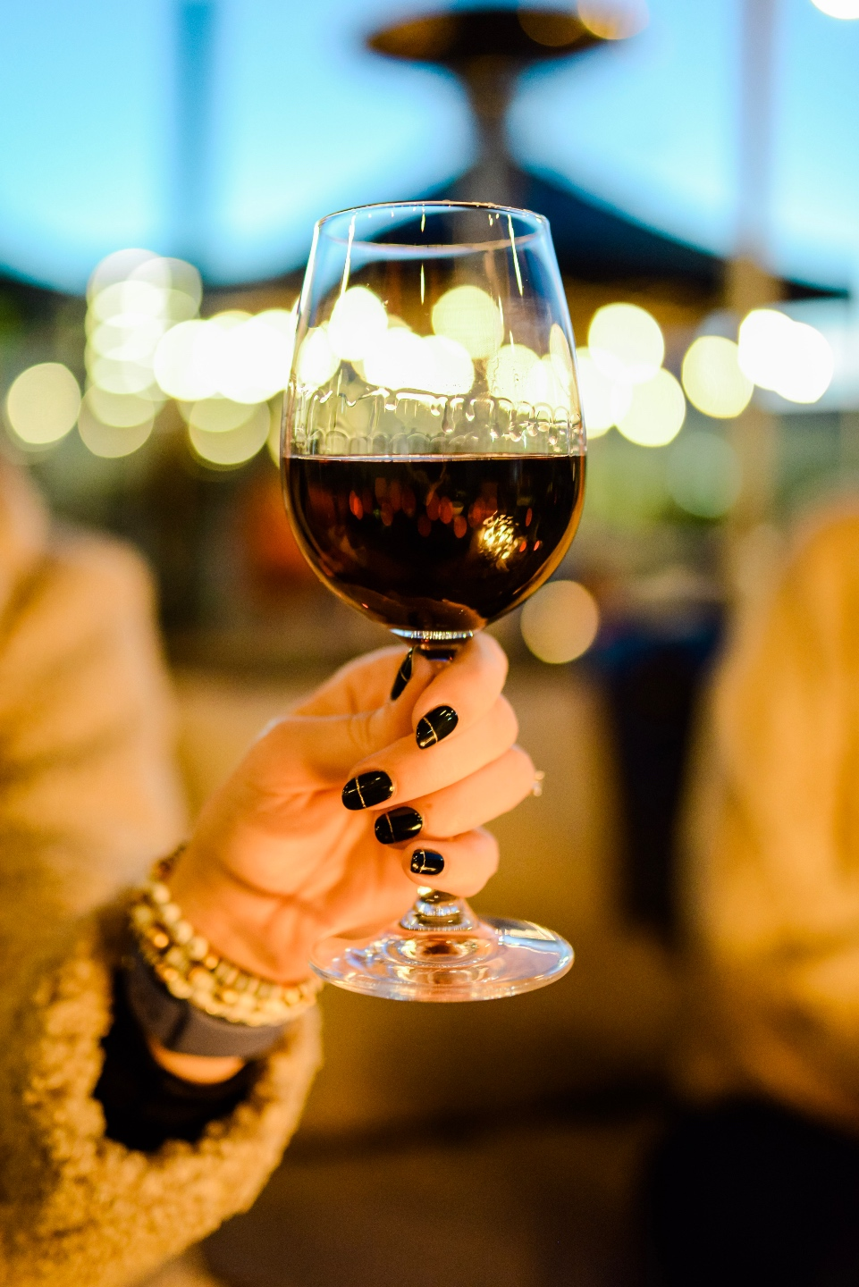 Restaurants with Patios in the Triangle by popular NC lifestyle blog, I'm Fixin' To: image of a woman holding a glass of wine.