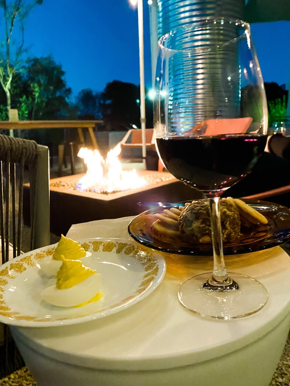 Restaurants with Patios in the Triangle by popular NC lifestyle blog, I'm Fixin' To: image of crackers, a cheese ball, deviled eggs, and a glass of red wine.