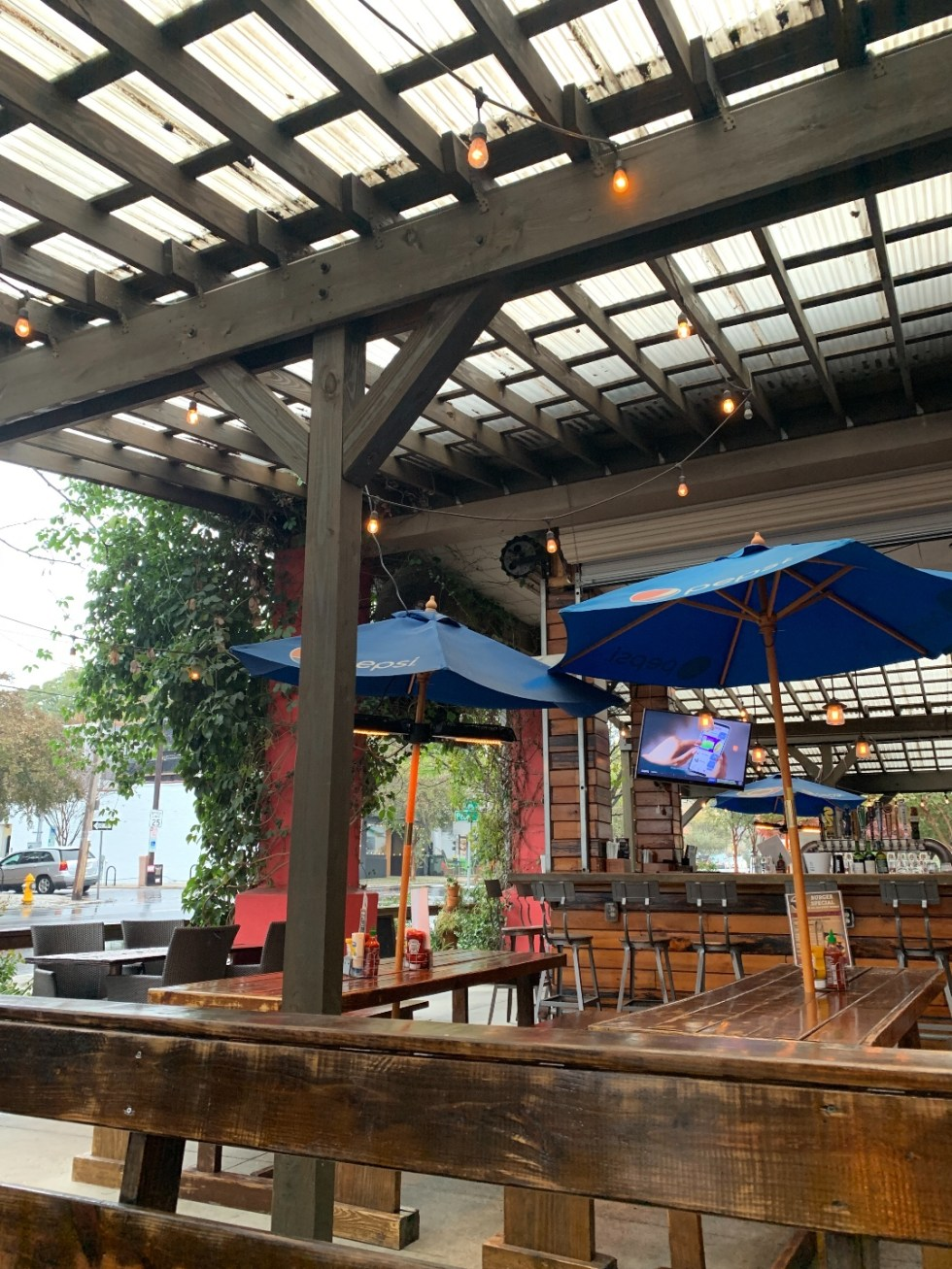 Restaurants with Patios in the Triangle by popular NC lifestyle blog, I'm Fixin' To: image of a covered patio with wooden tables and blue shade umbrellas.
