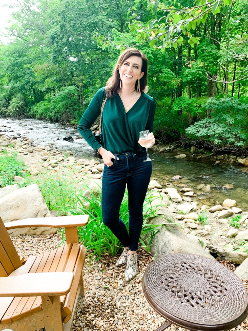 Most Popular Posts of 2020 - I'm Fixin' To - @imfixintoblog |Most Popular Posts by popular NC lifestyle blog, I'm Fixin' To: image of a woman standing by a river and and wearing a green long sleeve body suite, snake skin print ankle boots, jeans, and holding a glass of white wine.